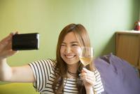 ワイングラスを持って自撮りをしている女性