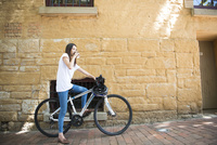 自転車にまたがってコーヒーを飲んでいる女性 10568004471| 写真素材・ストックフォト・画像・イラスト素材|アマナイメージズ