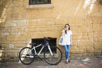 自転車の横でコーヒーを飲んでいる女性 10568004503  写真素材・ストックフォト・画像・イラスト素材 アマナイメージズ