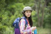 森の中で振り返っている女性 10568004560| 写真素材・ストックフォト・画像・イラスト素材|アマナイメージズ
