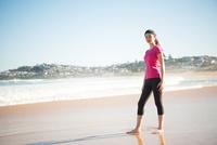 トレーニングウェアでビーチに立っている女性