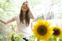 ひまわりと女性 10568005118| 写真素材・ストックフォト・画像・イラスト素材|アマナイメージズ