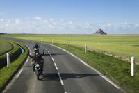 遥か遠くにモンサンミッシェルを望む田園地帯を走るバイク