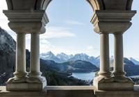ノイシュヴァンシュタイン城飾り柱越しに山並みと湖を見る