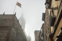 霧で霞むトレド大聖堂の尖塔を背景にスペイン国旗を見る 10573005627| 写真素材・ストックフォト・画像・イラスト素材|アマナイメージズ