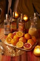 卓上でキャンドルに囲まれた 柑橘系フルーツと洋酒
