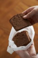 ワックスペーパーに包んだチョコのパウンドケーキを持つ女性