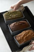 焼き上がったチョコと抹茶とナッツのパウンドケーキを持つ女性