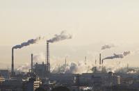 煙が立つ工場の朝の風景