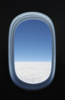飛行機の窓と雲の上の風景