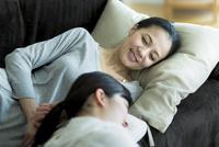 ソファーでくつろぐ母親と娘