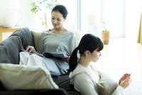 ソファーでくつろぐ母親と娘 10622000084| 写真素材・ストックフォト・画像・イラスト素材|アマナイメージズ
