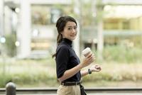 コーヒーを持ちながら歩くビジネスウーマン