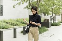 スマートフォンを見ながら歩くビジネスウーマン