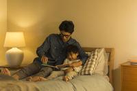 ベッドで絵本を読む父親と息子 10622000792| 写真素材・ストックフォト・画像・イラスト素材|アマナイメージズ