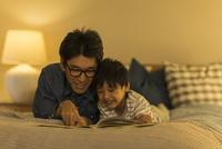 ベッドで絵本を読む父親と息子