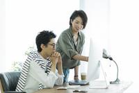 パソコンを見るビジネスマンとビジネスウーマン