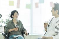 会話をするビジネスマンとビジネスウーマン 10622000891| 写真素材・ストックフォト・画像・イラスト素材|アマナイメージズ