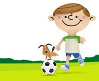 緑の上でサッカーボールを追いかける男の子と犬