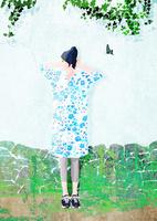 壁際で立つ女性