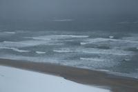 雪の鳥取砂丘と日本海の荒波