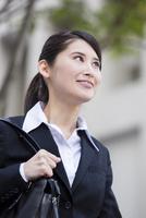 オフィス街を歩くスーツの女性