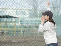 休日に子供の野球を応援する女性