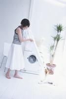 洗濯機の前の犬と女性