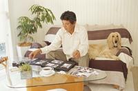 アルバムを整理する男性と犬