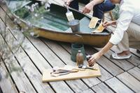 ボートにペンキを塗る男性と女性