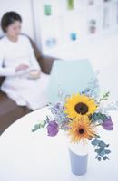 花のあるテーブルとソファに座っている女性