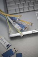 束ねたケーブルとノートパソコンとUSBメモリー