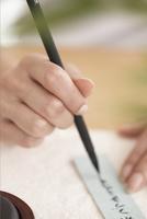 短冊に願い事を書く女性の手元