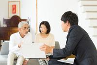 営業マンに説明を受ける中高年夫婦