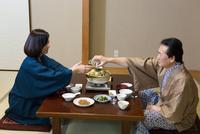旅館で料理を楽しむ夫婦