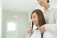 美容院で髪を切る若い女性