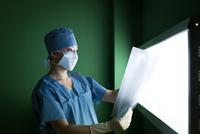 レントゲン写真を見る手術着を着た女医