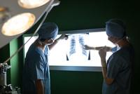 レントゲン写真を見る手術着を着た医療スタッフ