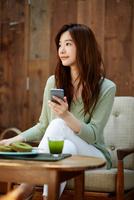 カフェで携帯電話を使う女性