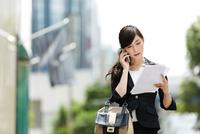 屋外で携帯電話を使うビジネスウーマン 10736003963| 写真素材・ストックフォト・画像・イラスト素材|アマナイメージズ