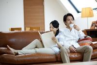 ソファで寛ぐ若い夫婦