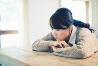 テーブルでリラックスする女性 10736005969  写真素材・ストックフォト・画像・イラスト素材 アマナイメージズ