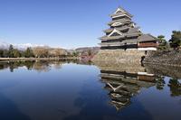 お堀に映り込む朝の松本城と北アルプス山脈