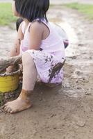 ワンピース姿で泥遊びをする女の子