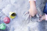 砂場で泥遊びをする子どもの手