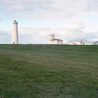 アイスランドのガーダーの灯台と家が遠くに見える草原