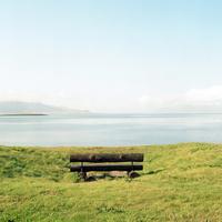 アイスランドのセルタルナルネスの海岸沿いの草原にある丸太のベンチ越しに見える海