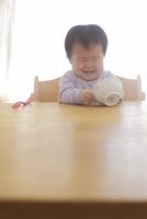 お茶碗に手を突っ込んで笑う赤ちゃん