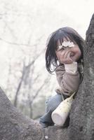 木に登って桜を見せる女の子
