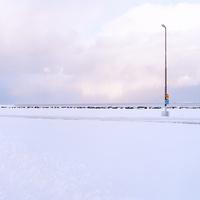 アイスランドの雪が積もり朝焼けが差す海岸通りと標識